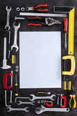 top view of set of various work tools and blank paper on black