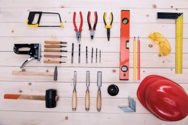Top view of set of construction tools and hard hat on wooden table