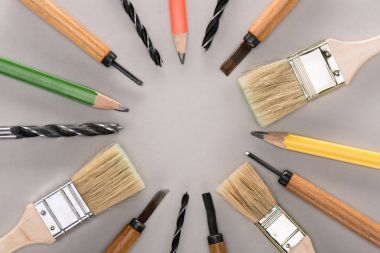 top view of various paint brushes, pencils, chisels and drills on grey