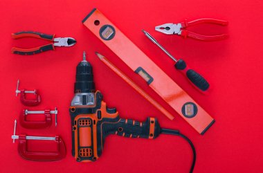 top view of various work tools and pencil on red