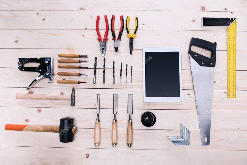 Top view of various construction tools and digital tablet on wooden table