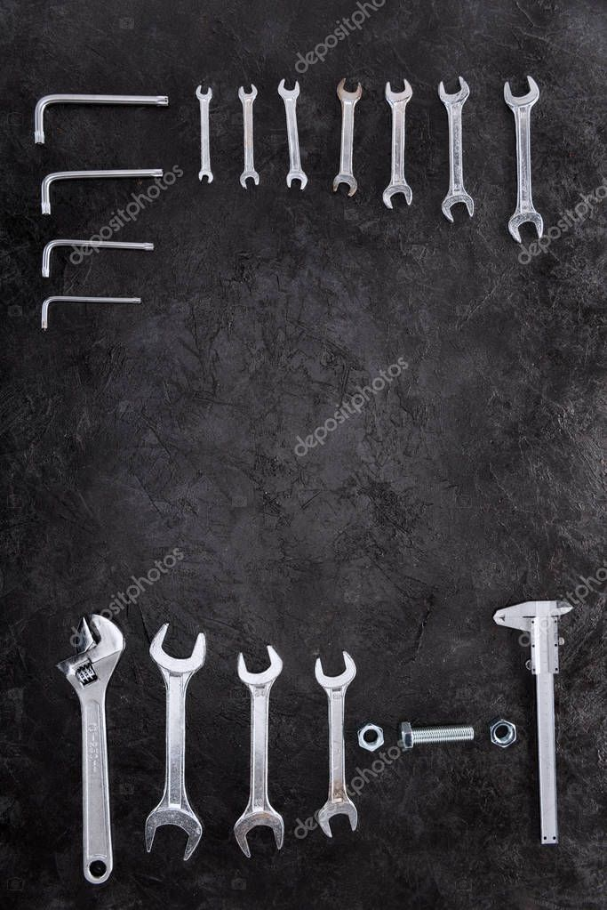 Top view of set of construction tools, wrenches and spanners on black stock vector