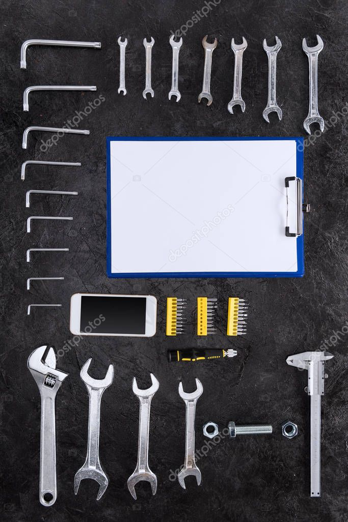 Top view of set of construction tools, smartphone and blank clipboard