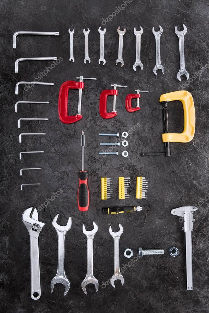Top view of set of different construction tools on black