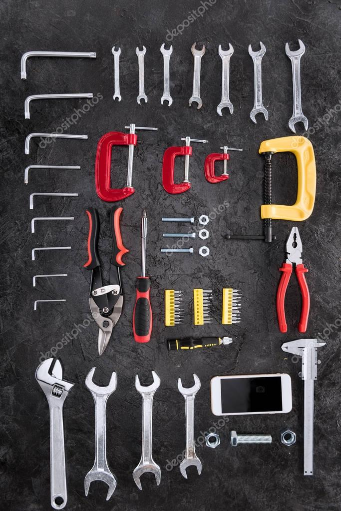 Top view of set of construction tools and smartphone on black