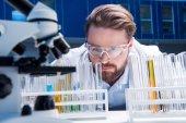 Fotografie Chemiker in Schutzbrille mit Reagenzien