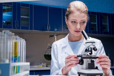 attractive scientist working with microscope