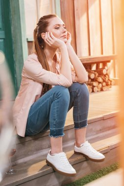 pensive woman sitting on porch