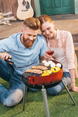 Man and woman roasting meat and vegetables on barbecue grill, woman holding wineglass stock vector