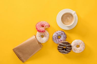 Top view of cup of coffee and several donuts scattered on yellow surface. donuts isolated on yellow background stock vector