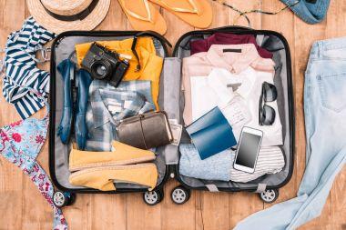 Overhead view of traveler's accessories organized in open luggage on wooden floor stock vector
