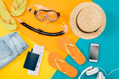 Overhead view of clothes, flip flops, tickets, headphones, smartphone and snorkeling equipment on colored background. Ready for summer vacation stock vector