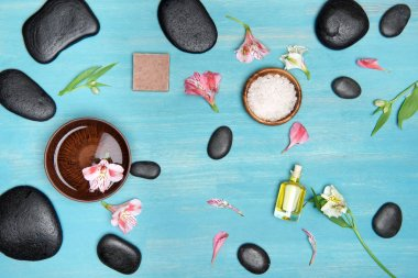 Top view of black spa stones, oil, sea salt and orchids on blue wooden table top stock vector