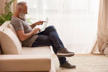 Senior man using laptop