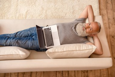 Senior bearded man with laptop, looking at camera and relaxing on sofa at home stock vector