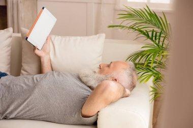 Senior bearded man using digital tablet and lying on sofa at home stock vector