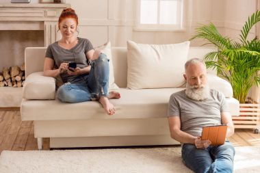 Husband using digital tablet and sitting on floor while wife using smartphone and sitting on sofa stock vector