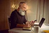 Grauhaariger Mann arbeitet zu Hause