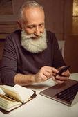 Lächelnder Mann mit Smartphone zu Hause