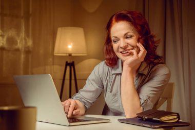 Smiling woman working on laptop