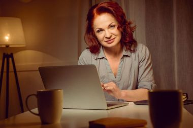 Woman working on laptop and looking at camera