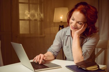 Red hair woman working on laptop