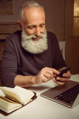 smiling man using smartphone at home