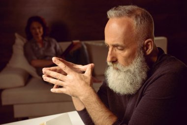 grey haired man sitting in thoughtful pose