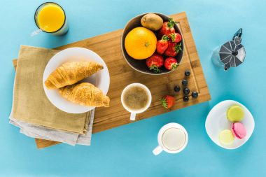 croissants with berries and coffee and orange juice