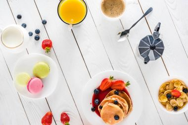 pancakes with macarons and coffee on wooden tabletop