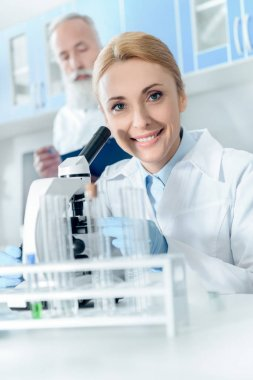 Caucasian smiling scientist in white coat working with microscope and reagents while looking at camera with colleague behind in lab stock vector