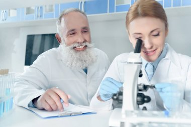 scientists in white coats in lab