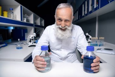 scientist holding bottles with reagents