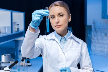 laboratory technician looking at tube with reagent
