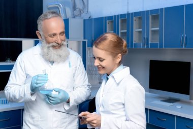 smiling chemists in lab coats at laboratory