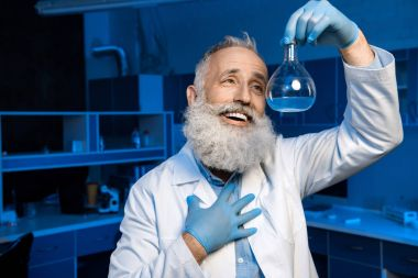 grey haired scientist holding flask