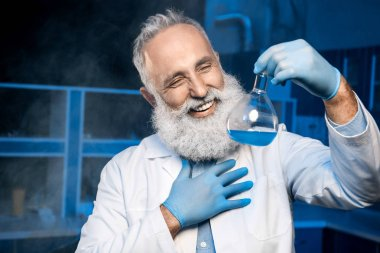 mature scientist holding flask with reagent