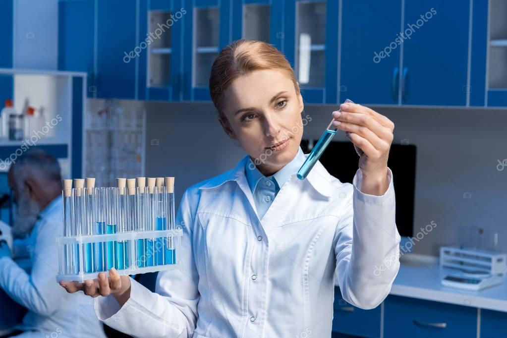 scientist in lab coat looking at tube