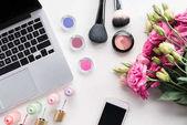 různé kosmetiky a laptop na stole