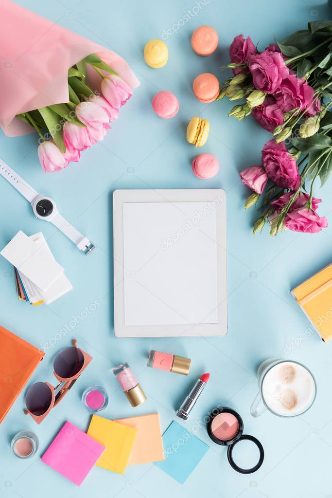 tablet, various accessories and flowers on tabletop