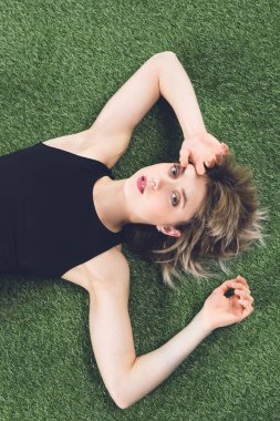 young caucasian woman lying on grass