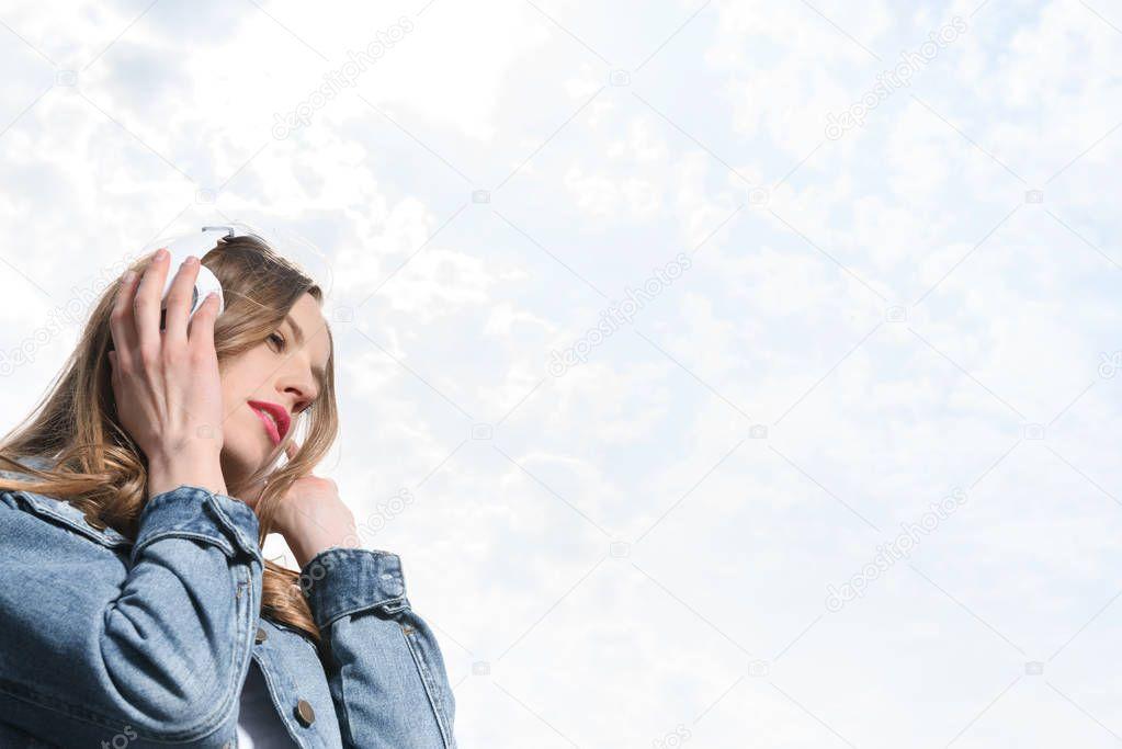 pensive girl listening music in headphones