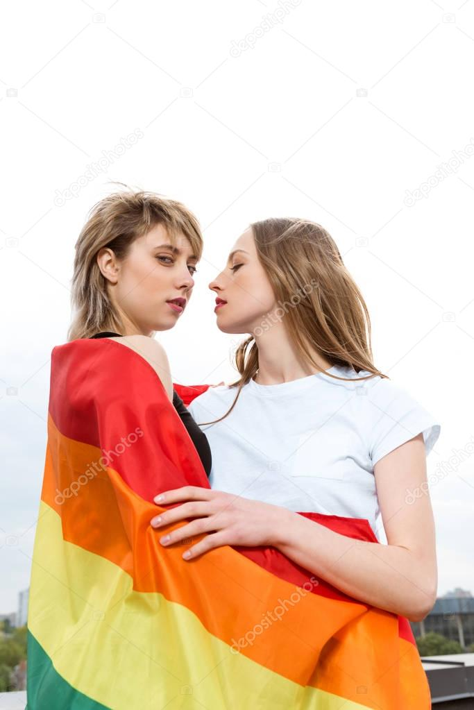 homosexual couple embracing with lgbt flag