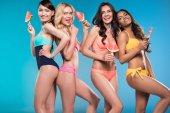 Frauen in Badeanzügen posieren mit Wassermelonenstücken