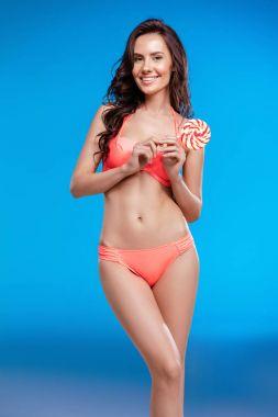 Girl in swimsuit holding lollipop