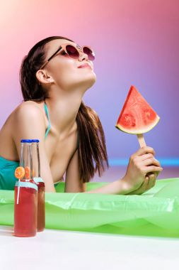 Girl in sunglasses sunbathing on swimming mattress