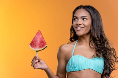 woman in swimwear holding watermelon piece