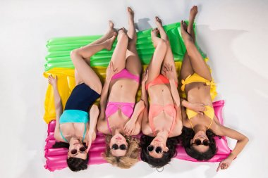 girls in swimsuits sunbathing on swimming mattresses