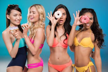 multiethnic women in swimsuits holding doughnuts