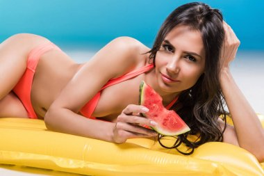 woman eating watermelon on swimming mattress